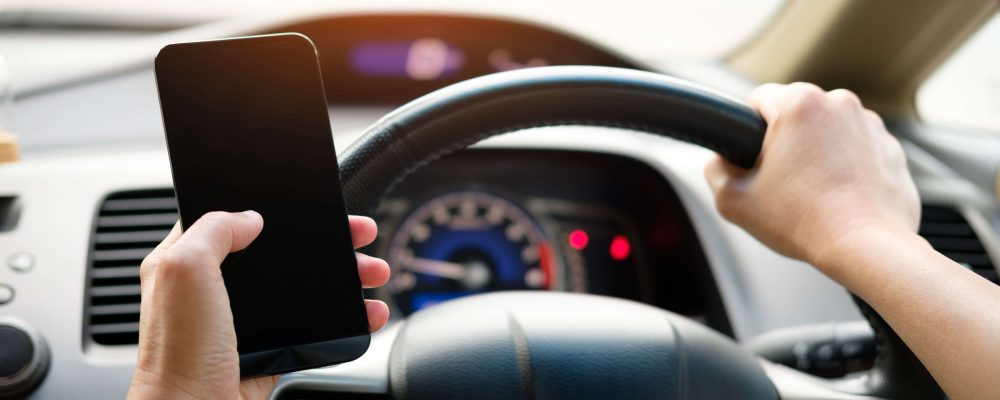 person-holding-black-smartphone-and-vehicle-steering-wheel-16.03.2020 (1)